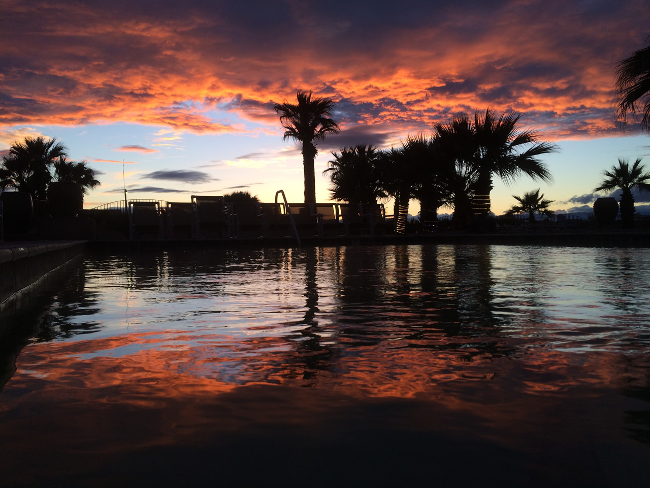 A picture of the sun setting over the Glamis North Hot Springs Resort pool complex